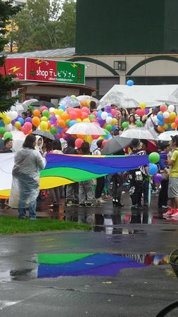 水たまりに虹色の旗が反射する。